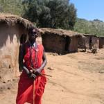 案内してくれたマサイの青年。学校に通い英語を学んだひとが観光客の相手をする。背後にあるのはマサイの家。牛の糞を乾かしたものを用い建てられる。家の建設は女性の仕事とか。