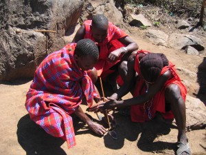 マサイの青年たちが、火起こしを実演。小さなくぼみのある木と棒を用意し、棒をくぼみに入れ回転させ摩擦で火種をつくり、煙が出てきたら藁に引火させる。やってみたら意外と簡単だった。