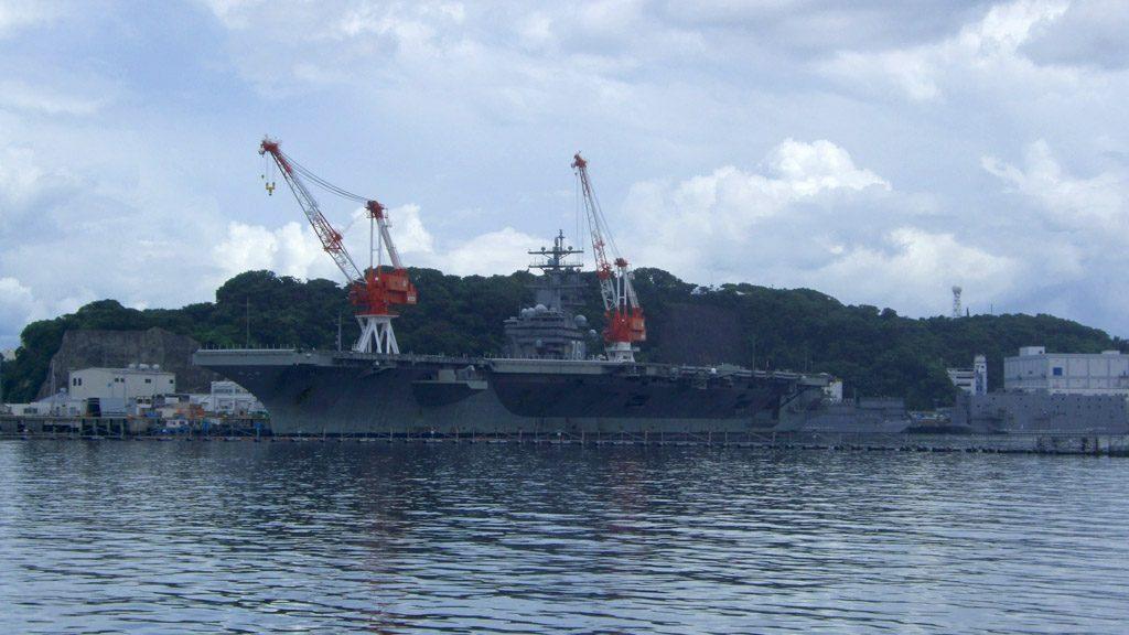 米海軍横須賀基地。写真は、空母専用埠頭「12号バース」に着艦する第7艦隊所属の原子力航空母艦「ロナルド・レーガン」だ。全長333mの巨大な体躯は通常陸からは見ることができないが、「軍港めぐりクルーズ」に参加することで間近に拝むことができる(もちろん帰還している間に限られる)。横須賀に空母が停泊しているということは、艦載機は厚木基地など他の場所に移されていることを意味する。海上自衛隊基地と隣り合う米軍横須賀基地は、アメリカ国外では唯一の(事実上の)空母の母港である。(撮影=bg)
